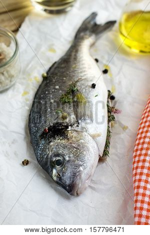 Fresh fish gilt-head bream dorade with salt herbs and pepper