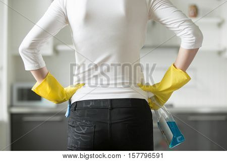Rear, closeup view at a young woman wearing rubber protective yellow gloves, holding rag and spray bottle detergent, hands at her hips. Ready to start or have just completed cleaning the kitchen. Home, housekeeping concept