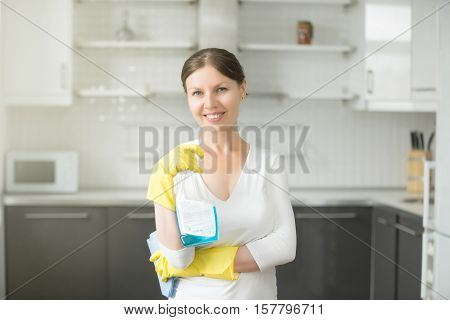 Portrait of smiling attractive young woman, wearing rubber protective yellow gloves, holding rag and spray bottle detergent. Home, housekeeping concept