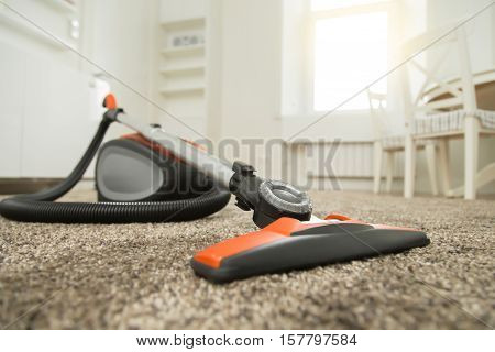 Black and orange vacuum cleaner standing on fluffy carpet in the living room before or after the cleaning. Home, housekeeping concept.
