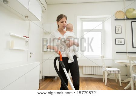 Frustrated woman cleaning carpet in living room holding newborn in one hand and vacuum cleaner in another, tired woman, combining doing many things, feels limiting at times. Home, housekeeping concept