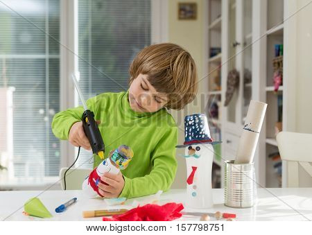 Little boy being creative making do-it-yourself toys out of yogurt bottle and paper using hot melt glue gun. Supporting creativity learning by doing hand craft. Creative leisure for children indoors.