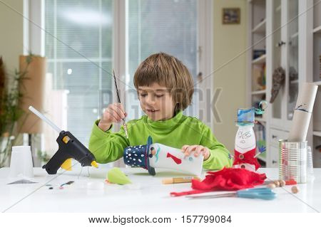 Little boy being creative painting dots on homemade do-it-yourself toys made of yogurt bottle and paper. Supporting creativity learning by doing hand craft. Creative leisure for children indoors.