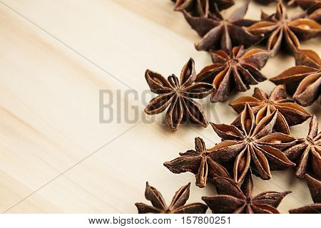 Anise star close up on wooden beige background. Decorative border of star anise spice on wood board.