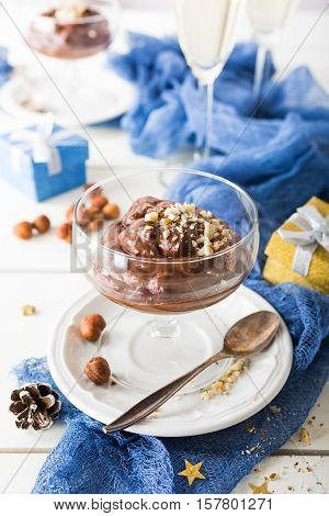 Chocolate pudding mousse with avocado, nuts and holiday decorations. Delicious Christmas themed dinner table.
