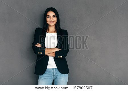 Confident and beautiful. Attractive young woman in smart casual wear keeping arms crossed and looking at camera with smile while standing against grey background