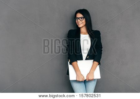 Young business expert. Attractive young woman in smart casual wear and eyeglasses carrying laptop and smiling while standing against grey background