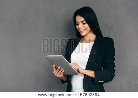 Examining her new tablet. Attractive young woman in smart casual wear working on digital tablet and smiling while standing against grey background