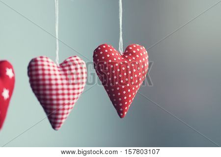 Beautiful red plush hearts hanging on rope with beautiful light on a colorful background horizontal valentine's day or love concept