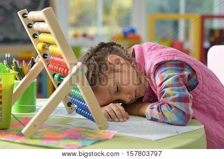 Tired preteen girl fell asleep when she does her homework