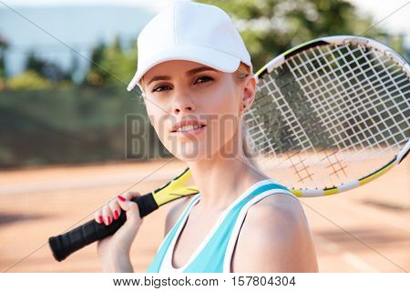Close up tennis woman. stands sideways on court with racket. looking at camera