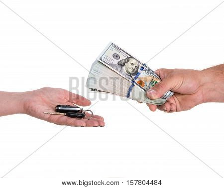 Female hand holding a car key and handing it over to another person.Man holding dollars