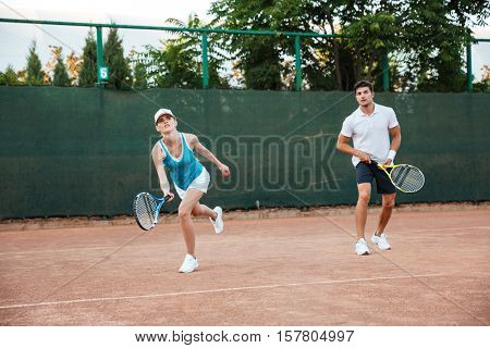 Young couple playing in tennis on court