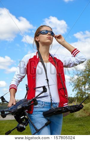 A brunette coed flying a drone in the outdoors