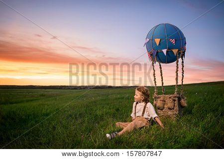 Little boy with aerostat in a field