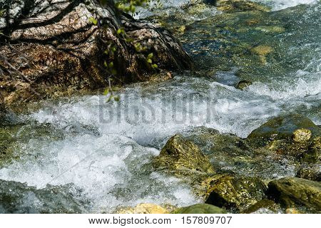 foamy, turbulent mountain stream passes through rocks with rock pattern