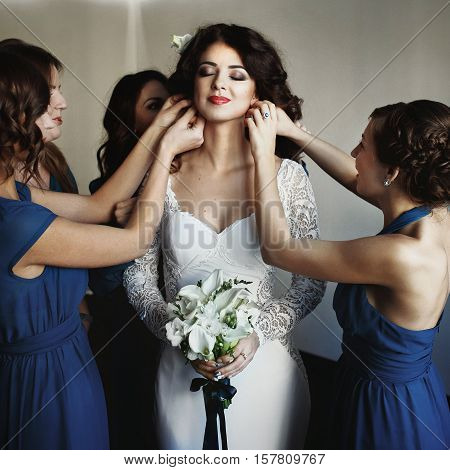 Bridesmaids put on the earrings on the bride