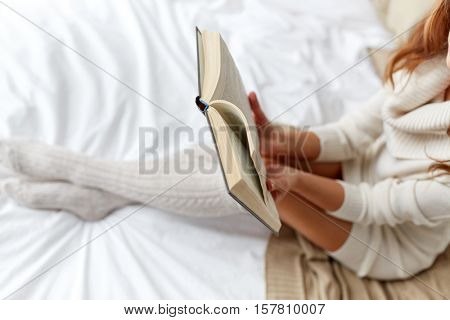 winter, coziness, leisure and people concept - close up of young woman reading book in bed at home