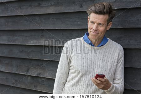 Portrait shot of an attractive, successful and happy middle aged man male outside using a mobile cell phone