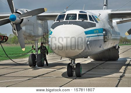 Vasilkov Ukraine - April 24 2012: Ukraine Air Force Antonov An-26 cargo plane is preparing to start the engines with the starter vehicle on the airfield