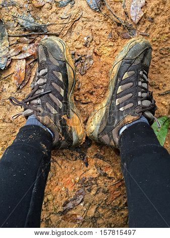 Woman with dirty brown hiking shoes resting on wet muddy area full of dried leaves