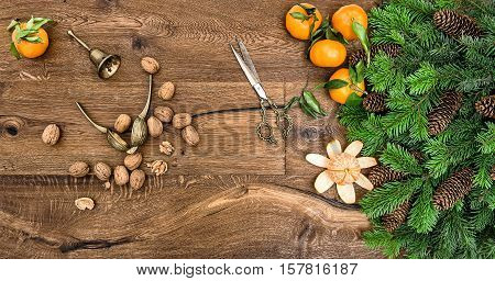 Orange mandarins walnuts and antique accessories. Christmas tree branches on wooden background