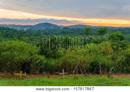 Simple wooden crosses and graves in front of lush jungle and dramatic sunset in Democratic Republic of Congo.