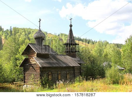 Wooden Church at the foot of the hill. Vintage wooden log Church. Wooden Christian timbered Church. Log building of the Christian Church