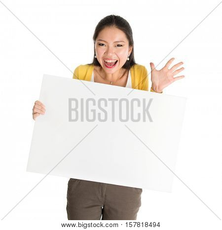 Portrait of surprised Asian girl hand holding blank white paper card and smiling excitedly, isolated on white background.