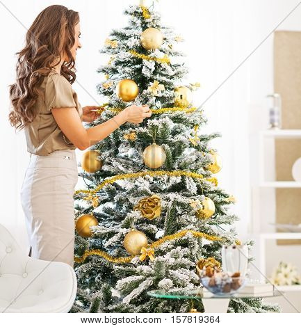 Full Length Portrait Of Young Woman Decorating Christmas Tree With Christmas Ball