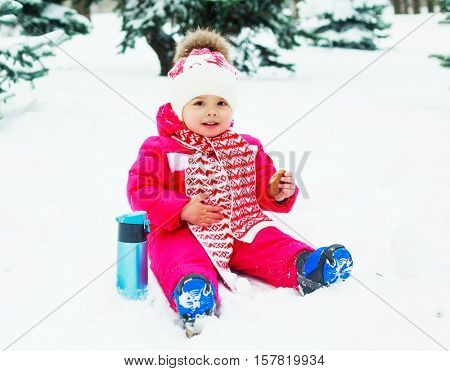 baby in the winter park drinking tea