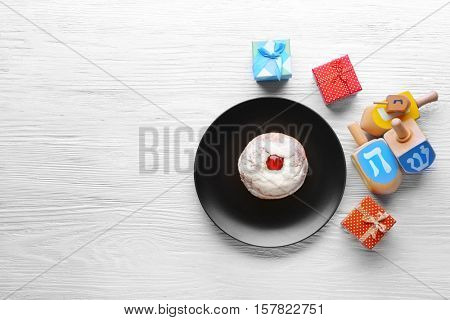 Composition of tasty donut, dreidels and presents for Hanukkah on wooden table