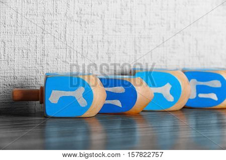 Dreidels for Hanukkah on wooden table against light textured wall