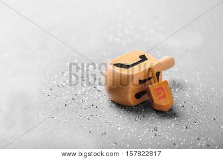 Wooden dreidels for Hanukkah on light background