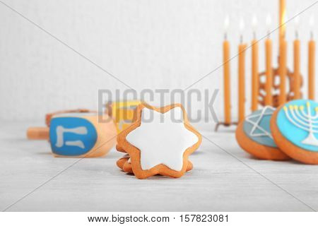 Tasty cookies for Hanukkah on wooden table against light background