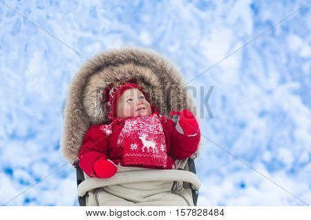 Happy laughing baby in warm red down jacket and knitted Nordic hat and scarf on a walk in a snowy winter park sitting in warm stroller with sheepskin hood catching snow. Child in buggy with foot muff