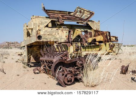 Abandoned harvester rusting away deep in the Namib Desert of Angola with fence in background.
