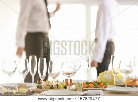 Close up view of table setting for holiday buffet, on blurred background