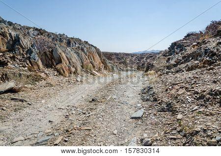 Track running through rocky arid desert scenery in ancient Namib Desert of Angola. The piste is rarely driven.