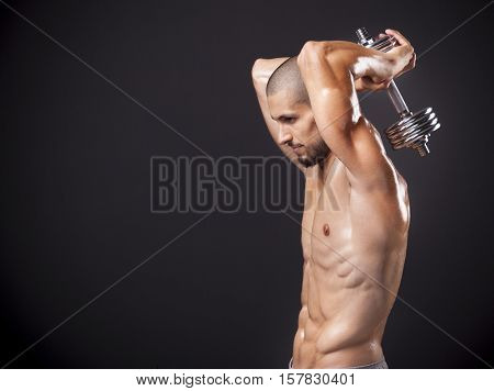 Young muscular man exercising his triceps with weights over dark background