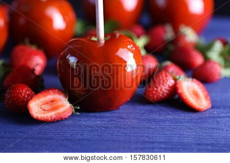 Candy apple with strawberries on wooden table closeup