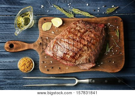 Delicious moist steak on board and blue wooden background