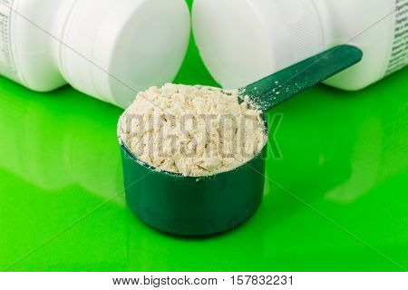 Protein powder in plastic spoon on green background
