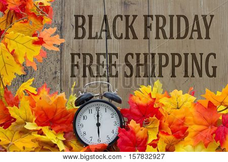 Time for Black Friday Free Shipping Autumn Leaves and Alarm Clock with grunge wood with text Black Friday Free Shipping