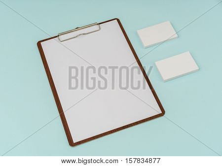 Clip board, paper and business card on blue background