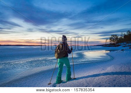 Woman Snowshoeing By The Lakeside