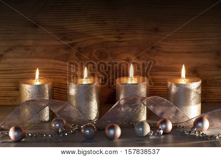 Christmas decoration in silver and pink with four noble candles in front of a dark wood background