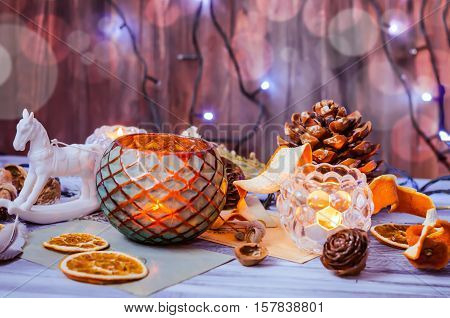 New year and Christmas winter decoration on rustic white wooden background with snow covered fir branches, tangerines, cones, candlestick, candle and orange slices. Bokeh