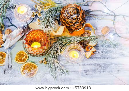 New year and Christmas winter decoration on rustic white wooden background with snow covered fir branches, tangerines, cones, candlestick, candle and orange slices. Top view, Copyspace background