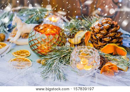 New year and Christmas winter decoration on rustic white wooden background with snow covered fir branches, tangerines, cones, candlestick, candle and orange slices.